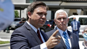 Florida Gov. Ron DeSantis, left, gestures as he speaks to the media with Vice President Mike Pence delivering personal protective equipment to the Westminster Baldwin Park, Wednesday, May 20, 2020, in Orlando, Fla. (AP Photo/Chris O'Meara)