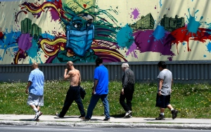People pass a mural of a person wearing a mask by artist Dom Laporte in Ottawa, on Sunday, May 24, 2020. (Justin Tang/THE CANADIAN PRESS)