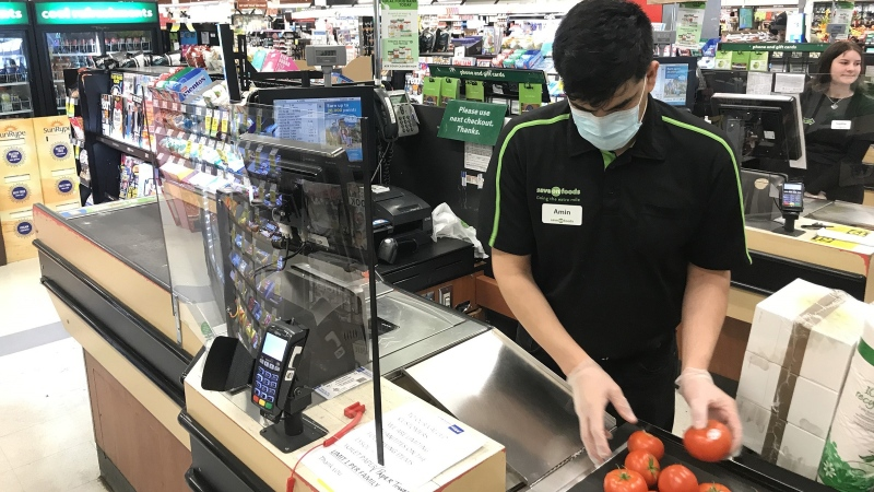 A plexiglass barrier is pictured creating a barrier to protect a cashier at a grocery store in North Vancouver, B.C., on Sunday, March 22, 2020. (Jonathan Hayward / THE CANADIAN PRESS)