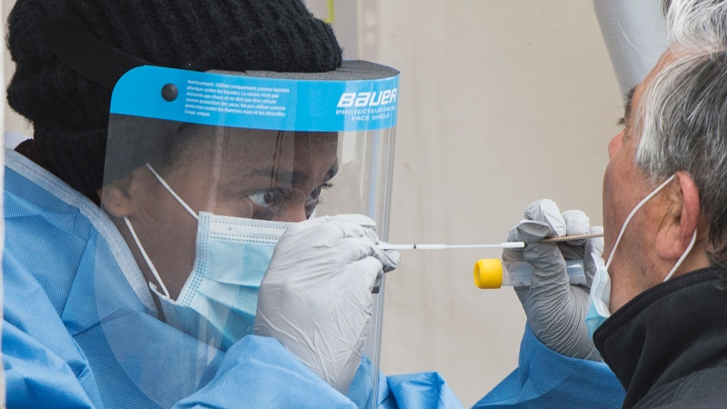 A health-care worker prepares to swab a man at a walk-in COVID-19 test clinic in Montreal North, Sunday, May 10, 2020, as the COVID-19 pandemic continues in Canada and around the world. THE CANADIAN PRESS/Graham Hughes