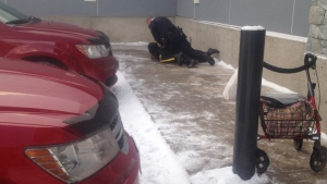 An RCMP officer tries to arrest Irene Josephs outside a Marks Work Wearhouse in Smithers, B.C. on Dec. 4, 2014 a few metres away from the walker she use for mobility. (Smithers Interior News)