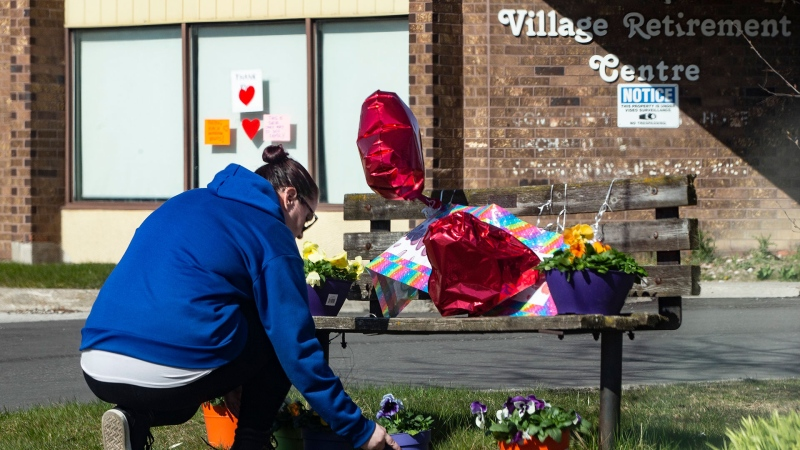 A woman lays flowers outside of Orchard Villa Care home, in Pickering, Ont. on Saturday, April 25, 2020. The care home has had over half it's residents tested positive for COVID-19. THE CANADIAN PRESS/Chris Young