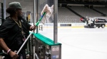 Lonnie Lockhart cleans the safety glass as the ice is resurfaced at American Airlines Arena, home of the Dallas Stars NHL hockey club, Thursday, March 12, 2020 in Dallas. The NHL announced Thursday it is suspending its season indefinitely in response to the coronavirus (Ashley Landis/The Dallas Morning News via AP)