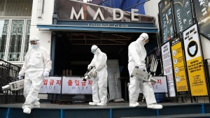 Workers spray disinfectant in front of the MADE, a major club in the international tourist district of Itaewon, in Seoul, South Korea, on May 12, 2020. (Lim Hun-jung/Yonhap via AP)