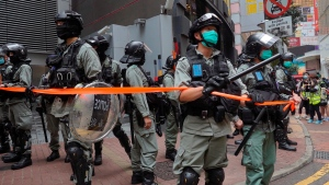 Riot police stand guard during a protest near Central Government Complex as a second reading of a controversial national anthem law takes place in Central district, Hong Kong, Wednesday, May 27, 2020. (AP Photo/Vincent Yu)