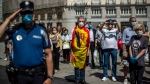 People hold a minute of silence for the victims of COVID-19 at Sol square in downtown Madrid, Spain, Wednesday, May 27, 2020. (AP Photo/Manu Fernandez)