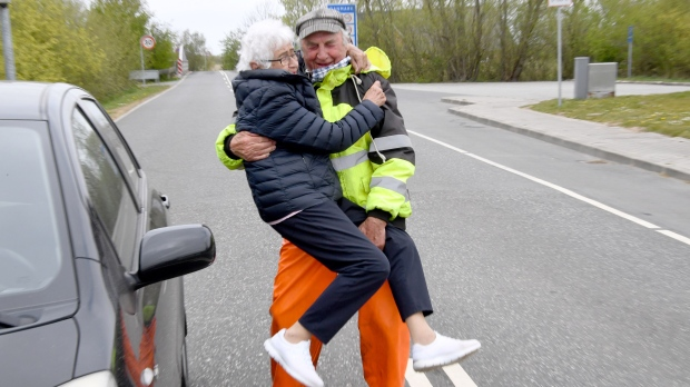 Inga Rasmussen, left, from Denmark is lifted up by Karsten Tüchsen Hansen from North Frisia, Germany, during their daily meeting at the German-Danish border on April 24. (Carsten Rehder/Picture Alliance/Getty Images)