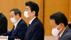 Japan's Prime Minister Shinzo Abe, center, speaks during a meeting of government and ruling party officials at his office in Tokyo Wednesday, May 27, 2020. (Kyodo News via AP)