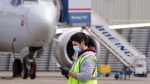 A worker walks past a Boeing 737 MAX jet at a Boeing airplane manufacturing plant Wednesday, April 29, 2020, in Renton, Wash. (AP Photo/Elaine Thompson)