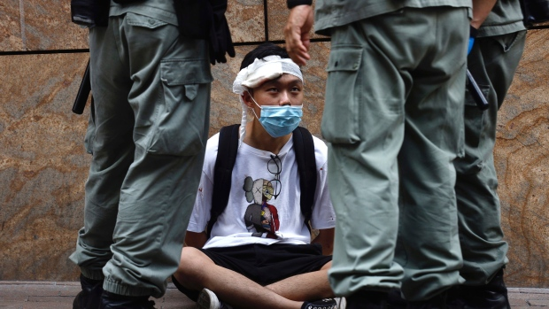 Riot police guard detain a protester as a second reading of a controversial national anthem law takes place in Central district, Hong Kong, Wednesday, May 27, 2020. (AP Photo/Kin Cheung)