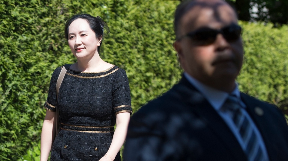 A security guard looks on as Meng Wanzhou, chief financial officer of Huawei, leaves her home to go to B.C. Supreme Court in Vancouver, Wednesday, May 27, 2020. THE CANADIAN PRESS/Jonathan Hayward