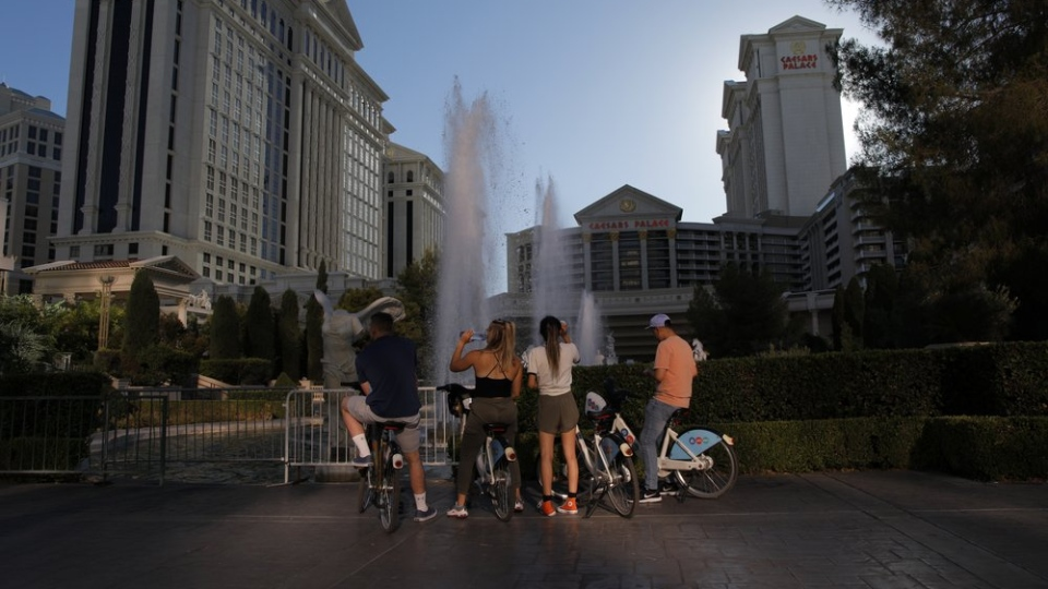 People stop to look at the fountains at Caesars Palace hotel and casino along the Las Vegas Strip devoid of the usual crowds during the coronavirus pandemic, Tuesday, May 26, 2020, in Las Vegas. (AP Photo/John Locher)
