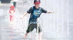 Seven-year-old Samuel Bedard from Quebec City runs through a water fountain as he beats the heat during a heatwave in Montreal, Monday, July 2, 2018. THE CANADIAN PRESS/Graham Hughes