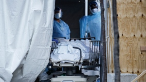 In this April 6, 2020, file photo, medical workers wearing personal protective equipment intake bodies through a tent before loading them onto a refrigerated trailer serving as a makeshift morgue at Wyckoff Heights Medical Center, in the Brooklyn borough of New York. (AP Photo/John Minchillo, File)