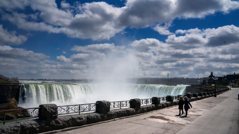 Two women walk along the deserted path beside Niagara Falls on Wednesday, April 22, 2020. THE CANADIAN PRESS/Frank Gunn