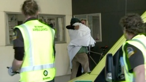 In this image made from May 27, 2020, video, one of the two hikers found alive is wrapped in a white blanket hugs another person as they enter a hospital in Nelson, New Zealand. (Newshub/TVNZ via AP)