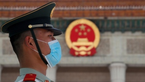 A paramilitary policeman wearing a mask is seen before the closing session of the Chinese People's Political Consultative Conference (CPPCC) at the Great Hall of the People in Beijing Wednesday, May 27, 2020. (AP Photo/Andy Wong)