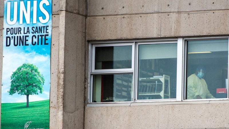 A health-care worker is seen in the window of the Centre d'hebergement Sainte-Dorothee, Thursday, April 9, 2020 in Laval Que. The residence has reported over 100 confirmed cases of COVID-19.THE CANADIAN PRESS/Ryan Remiorz