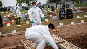 In this Wednesday April 8, 2020 file photo, a rabbi, background, finishes a prayer during a burial service as gravediggers prepare a plot for the next burial at a cemetery in the Staten Island borough of New York. (AP / David Goldman)