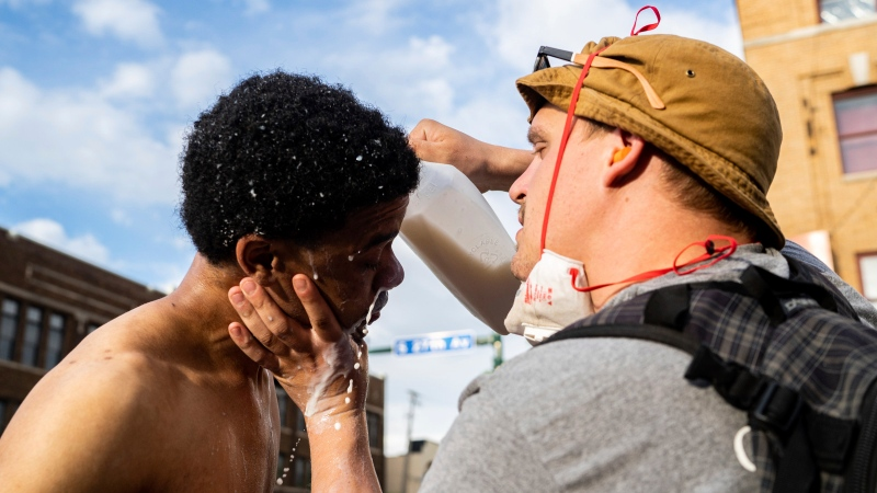 A man pours milk onto the face and eyes of another during protests Wednesday, May 27, 2020, in Minneapolis against the death of George Floyd in Minneapolis police custody earlier in the week. (Evan Frost/Minnesota Public Radio via AP)