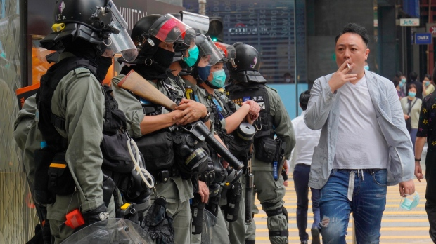 A man smokes past a line of riot police at Central during the second day of debate on a contentious bill that would criminalize insulting or abusing the Chinese national anthem, in Hong Kong, Thursday, May 28, 2020. (AP Photo/Vincent Yu)