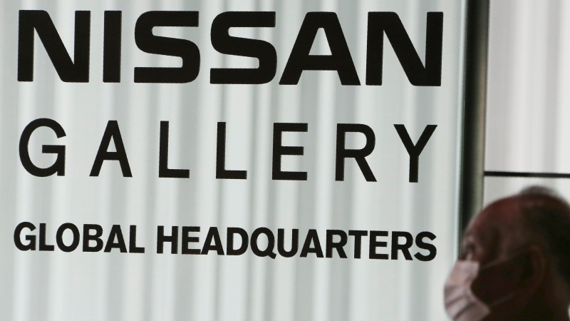 A man walks past the global headquarters of Nissan Motor Co., Ltd. in Yokohama near Tokyo, Wednesday, May 27, 2020. (AP Photo/Koji Sasahara)