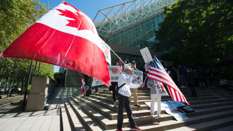 A crowd is pictured on the steps of B.C. Supreme Court as Meng Wanzhou, chief financial officer of Huawei, attends a session in Vancouver, on May 27, 2020. (Jonathan Hayward / THE CANADIAN PRESS)