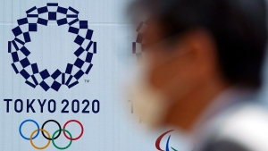 "In this April 2, 2020, file photo, a man wearing a face mask walks near the logo of the Tokyo 2020 Olympics, in Tokyo. Tokyo organizers said Tuesday, April 14, 2020 they have no ""B Plan"" for again rescheduling the Olympics, which were postponed until next year by the virus pandemic. They say they are going forward under the assumption the Olympics will open on July 23, 2021. (AP Photo/Eugene Hoshiko, File)"