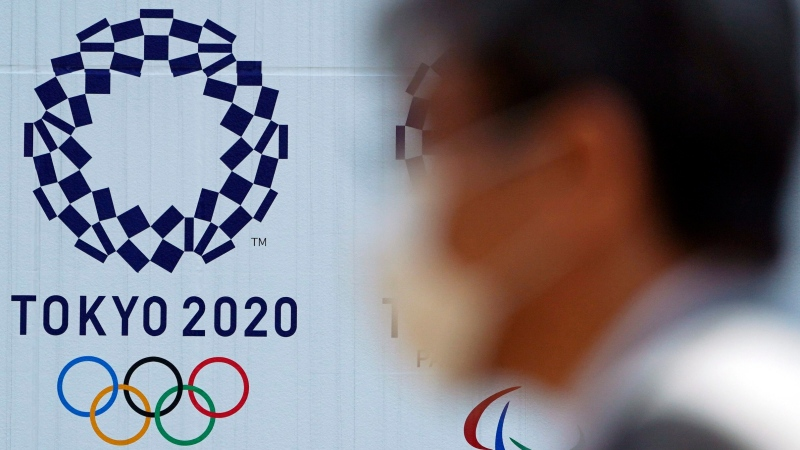 In this April 2, 2020, file photo, a man wearing a face mask walks near the logo of the Tokyo 2020 Olympics, in Tokyo. (AP Photo/Eugene Hoshiko, File)