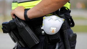 In this March 16, 2020, photo a North Charleston police officer carries a protective mask around his gun belt while working traffic at Roper St. Francis' North Charleston office in North Charleston, S.C. (AP Photo/Mic Smith, File)