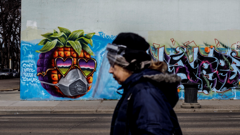 A person wearing a protective face shield walks past a mural during the COVID-19 Pandemic, in Edmonton Alta, on Wednesday April 15, 2020. THE CANADIAN PRESS/Jason Franson​