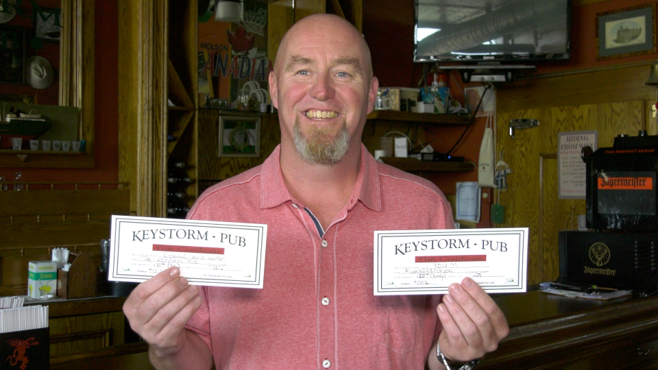 Dan Thompson shows off Keystorm Pub gift cards that are being given to front-line workers in Brockville. (Nathan Vandermeer / CTV News Ottawa)