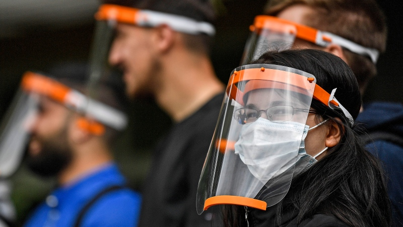 Students try out a new face shield to fight the coronavirus pandemic at a school in Cologne, Germany, Monday, May 25, 2020. (AP Photo/Martin Meissner)