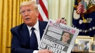 U.S. President Donald Trump holds up a copy of the New York Post as speaks before signing an executive order aimed at curbing protections for social media giants, in the Oval Office of the White House, Thursday, May 28, 2020, in Washington. (AP Photo/Evan Vucci)
