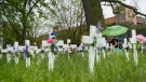 Innis Ingram sits chained to a tree where crosses lay identifying the lives lost to COVID-19 at the Camilla Care Community centre during the COVID-19 pandemic in Mississauga, Ont., on Thursday, May 28, 2020.  THE CANADIAN PRESS/Nathan Denette