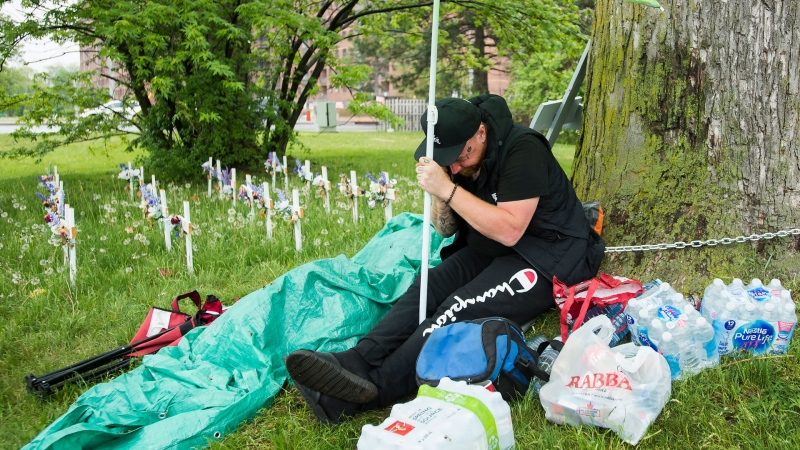 Innis Ingram sits chained to a tree where crosses lay identifying the lives lost to COVID-19 at the Camilla Care Community centre during the COVID-19 pandemic in Mississauga, Ont., on Thursday, May 28, 2020. Ingram's mother is inside the facility and he won't un-chain himself until a inspector arrives or management from Trillium Health Partners arrives. THE CANADIAN PRESS/Nathan Denette