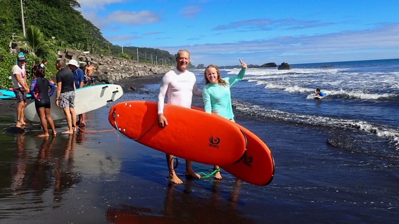 Kristen Pankratz, right, and her father David pose ahead of a surf in Tahiti on May 19, 2020. Since she was 4 years old, Kristen Pankratz has shared in dad's dream to sail around the world. Pankratz gave up her advertising job in Dallas and set sail with her parents in January. But now, along with hundreds of other sailors, the family finds themselves stranded in paradise.They made it as far as Tahiti in remote French Polynesia, one of the last places to offer refuge as borders slammed shut. (Kristen Pankaratz via AP)