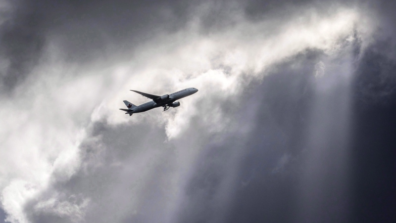 An Air Canada plane flies underneath dark clouds illuminated by some sun rays above Frankfurt, Germany, Thursday, March 2, 2017. Aimia Inc. says it plans to defend itself against a move by Air Canada in Quebec Superior Court to halt a merger that the smaller company sees as key to its corporate reinvention. THE CANADIAN PRESS/AP-Frank Rumpenhorst/dpa via AP