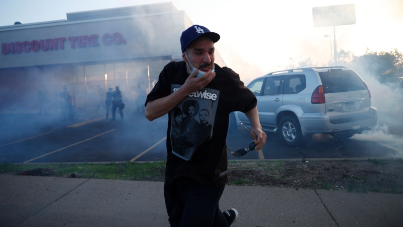 A demonstrator runs from tear gas Thursday, May 28, 2020, in St. Paul, Minn. (AP / John Minchillo)