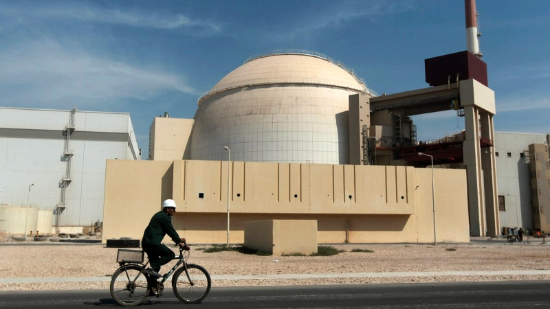 In this Oct. 26, 2010, file photo, a worker rides a bicycle in front of the reactor building of the Bushehr nuclear power plant, just outside the southern city of Bushehr. (AP Photo/Mehr News Agency, Majid Asgaripour, File)