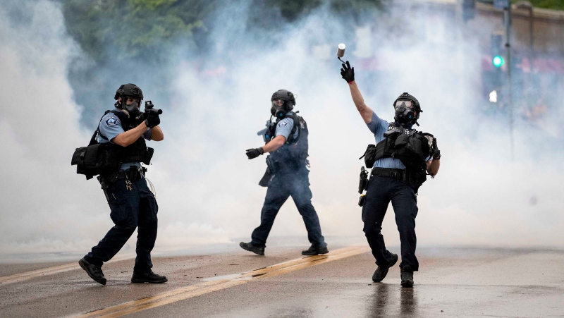 A police officer throws a tear gas canister towards protesters at the Minneapolis 3rd Police Precinct, following a rally for George Floyd on Tuesday, May 26, 2020, in Minneapolis. (Carlos Gonzalez/AP)