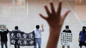 Protesters gesture with five fingers, signifying the 'Five demands - not one less' in a shopping mall during a protest against China's national security legislation for the city, in Hong Kong, on May 29, 2020. (Kin Cheung / AP)