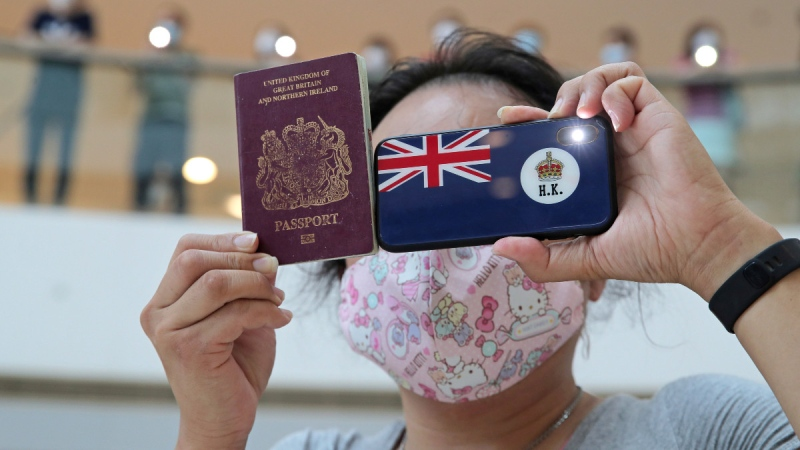 A protester holds a British National (Overseas) passport in a shopping mall during a protest against China's national security legislation for the city, in Hong Kong, on May 29, 2020. (Kin Cheung / AP)
