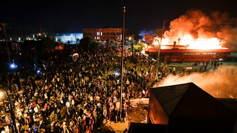Protestors demonstrate outside of a burning Minneapolis 3rd Police Precinct, Thursday, May 28, 2020, in Minneapolis. (AP Photo/John Minchillo)