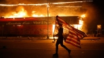 A protester carries a U.S. flag upside, a sign of distress, next to a burning building Thursday, May 28, 2020, in Minneapolis. THE CANADIAN PRESS/AP-Julio Cortez