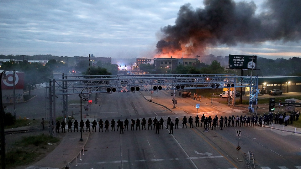 Law enforcement officers amassed along Lake Street near Hiawatha Ave. as fires burned after a night of unrest and protests in the death of George Floyd early Friday, May 29, 2020 in Minneapolis. Floyd died after being restrained by Minneapolis police officers on Memorial Day. (David Joles/Star Tribune via AP)