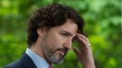 Prime Minister Justin Trudeau touches his forehead during a news conference outside Rideau Cottage in Ottawa, Friday May 29, 2020. THE CANADIAN PRESS/Adrian Wyld