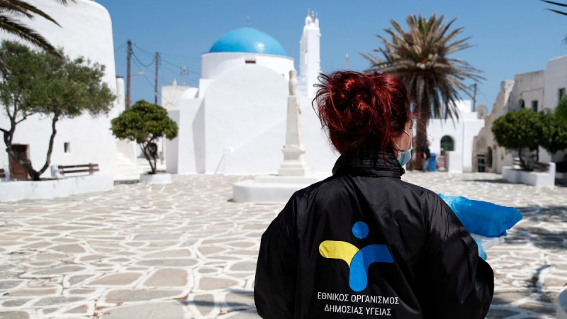 A doctor of the National Health Organization (EODY) carries the tests for coronavirus taken on local residents on the Aegean Sea island of Sikinos, Greece, on May 25, 2020. (Thanassis Stavrakis / AP)