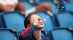 A young boy blows bubbles in the stands during the Women's World Cup Group B soccer match between China and Spain at the Stade Oceane in Le Havre, France, Monday, June 17, 2019. (AP Photo/Francisco Seco)