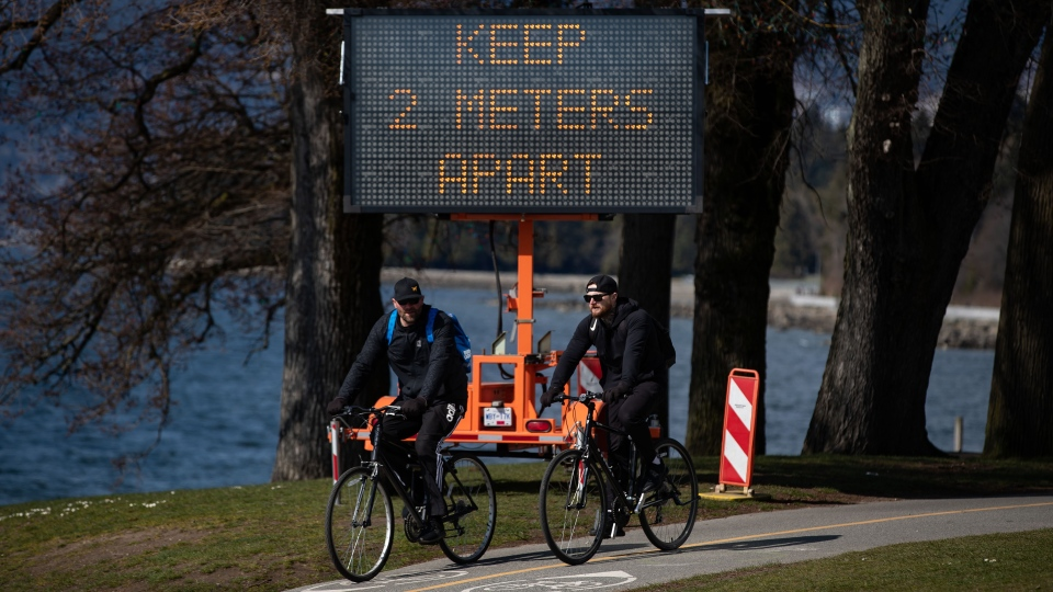 A sign warns people to social distance and keep at least 2 metres apart from one another due to concerns about the spread of the coronavirus, as two men ride bicycles on the seawall, in Vancouver, on Wednesday, March 25, 2020. (THE CANADIAN PRESS/Darryl Dyck)